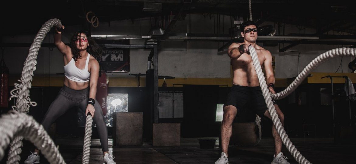 man and woman holding battle ropes in hiit training